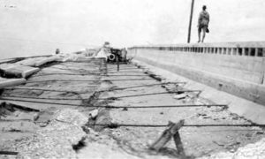 G-17713FF3.1-10 Man walking on top of guardrail of damaged causeway