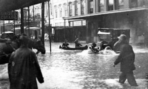 G-17713FF4.1-7 Pedestrians and automobile proceeding through flooded downtown street.