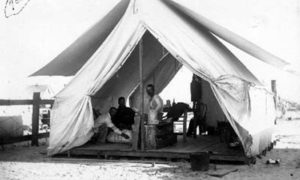 G-1771FF10.1-3 Three men seated inside tent