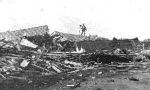 G-1771FF7.12-10 Photographer with his camera standing on roof of demolished house