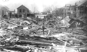 G-1771FF7.3-13 Worker standing amid debris, with wrecked houses.