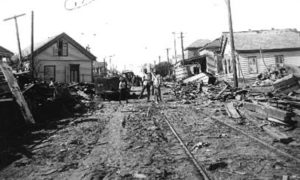 G-1771FF7.3-4 Looking down street lined with wrecked houses and debris