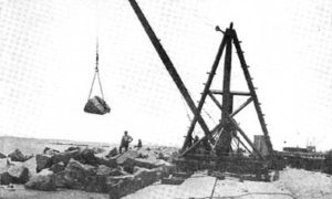 "G-5925.1FF3-3 THE GALVESTON SEAWALL.""  ""DERRICK LAYING RIPRAP.  A1500 LB. ROCK IN MIDAIR."