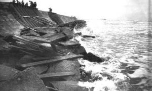 G-5925.3 FF6-7 Waves crashing against riprap, strewn with wood from caissons no longer in use