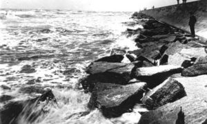 G-5925.3FF6-8 People standing and watching waves crash against riprap at base of Seawall
