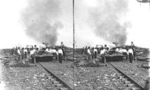 SC#194-22 Workmen clearing debris along railroad tracks.