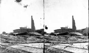 SC#194-41 Railroad track (foreground) and debris and wrecked businesses (background).
