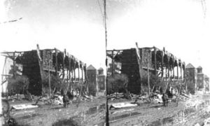 SC#194-6 People in horse and buggy going down street amid debris.