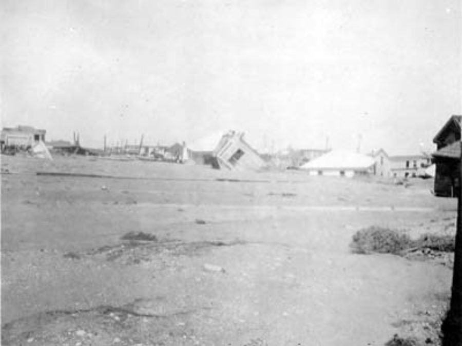 G-17713FF9.2-13 Wrecked and toppled houses partially submerged in sand