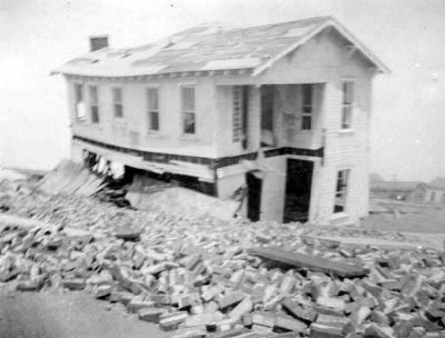 G-17713FF9.2-8 Wrecked two-story frame house viewed behind pile of bricks