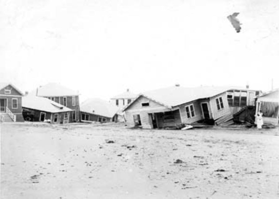 G-17713FF9.3-9 Row of wrecked houses partially submerged in sand.