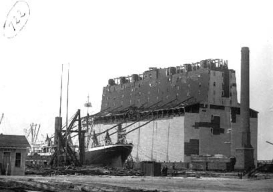 G-1771FF2.2-7 Steamship tied up next to wrecked grain elevator