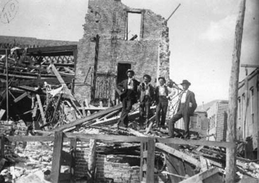 G-1771FF6.1-8 Four men posed standing on debris from Grand Opera House
