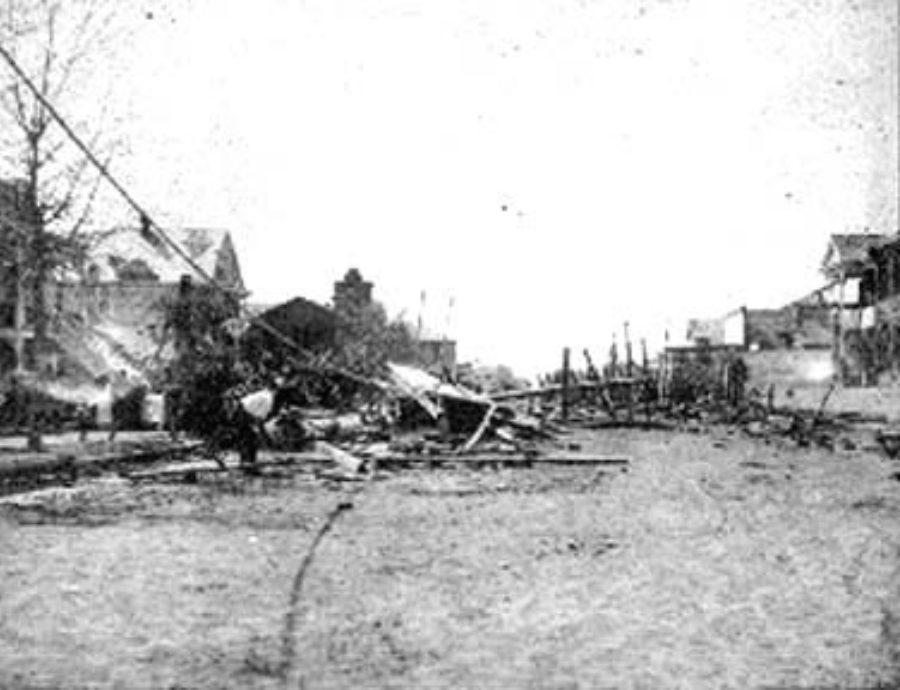 G-1771FF7.11-13 Man examining debris in residential street