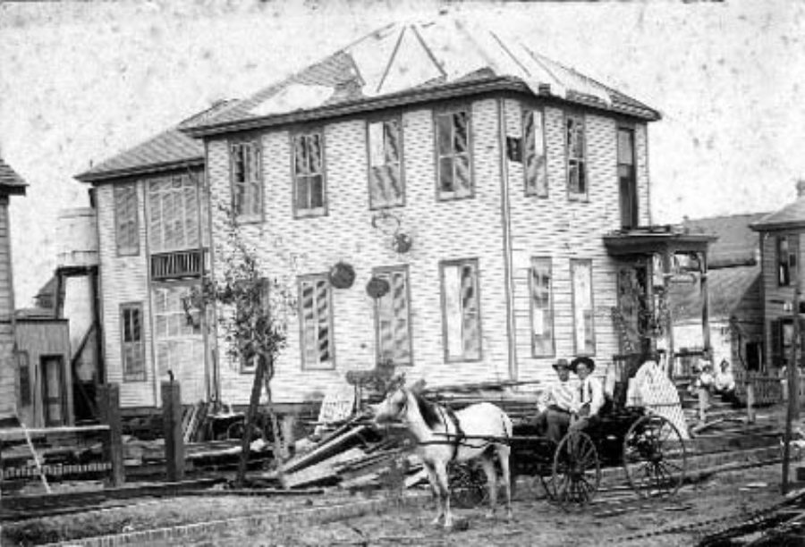 G-1771FF7.14-10 Two men seated in buggy in front of damaged two-story house