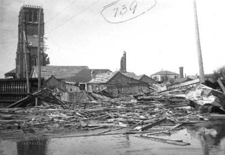 G-1771FF7.3-10 Standing water and debris (foreground).  Wrecked houses and church (background)