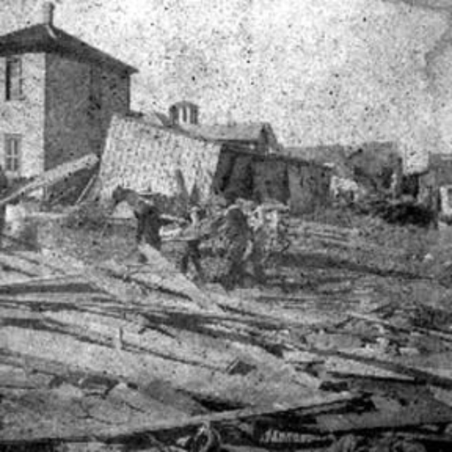 G-1771FF7.8-10 Workers carrying body past debris and wrecked houses