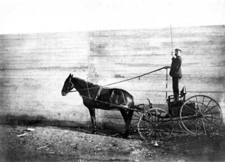 G-5925.3FF2-14 Man standing on buggy and holding reins to horse behind Seawall