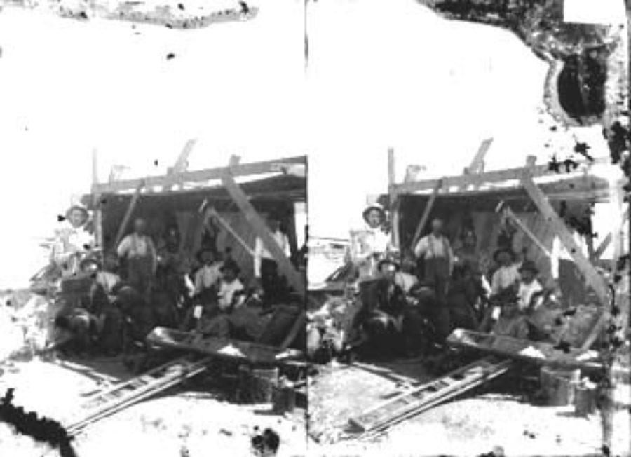 SC#194-14 Workmen taking break under lean-to shelter.