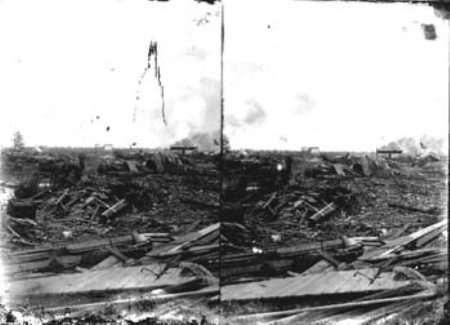 SC#194-42 Distant view of men with horse and buggy amid debris.